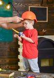 站立在与各种各样的工具的桌后的男孩 保重关于儿子安全的爸爸 拿着桔子的男性手 免版税库存图片