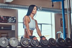 站立在与哑铃的柜台附近的运动服的美丽的性感的运动深色的女性在健身房 免版税库存图片