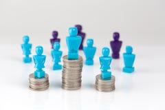 站立在与在地平线上方的硬币堆顶部的男性和女性小雕象 免版税库存图片