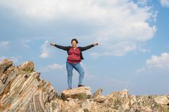 站立在与她的胳膊的五颜六色的岩石的亚裔妇女在a 库存图片