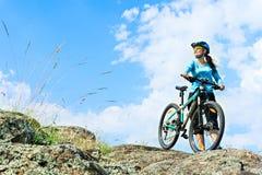站立在与她的mou的一个岩石的成人可爱的女性骑自行车者 免版税库存照片
