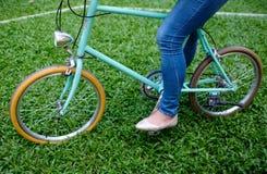 站立在与妇女的绿草的葡萄酒样式蓝色自行车牛仔裤的 库存照片