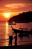 站立在与小船和日落天空背景的海滨附近的家庭剪影 库存照片