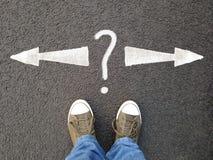 站立在与左右指向与问号的箭头的沥青的脚 免版税库存照片