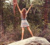 站立在与开放胳膊的大岩石的青少年的女孩 免版税图库摄影