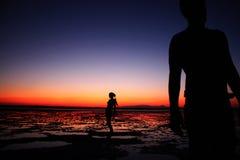 站立在与惊人的五颜六色的日落的海滩的两个人在背景 免版税库存图片