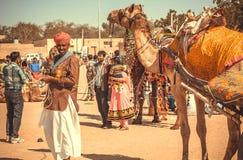 站立在与手机的一个动物附近的农村骆驼车手在手上在沙漠节日期间 免版税库存图片