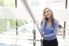 站立在与手机的一个现代大厦的女实业家 免版税图库摄影
