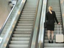 站立在与旅行袋子的自动扶梯的女实业家 免版税库存图片