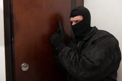 站立在与枪的门后的夜贼 库存图片