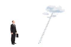 站立在与查寻的云彩的一架梯子前面的商人 免版税库存图片