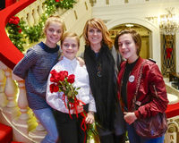 站立在与母亲和姐妹的一层红色楼梯的微笑的十岁的女孩 免版税库存照片