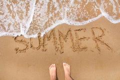 站立在与波动来的海滩沙子的女性脚顶视图  词在沙子的夏天文字 夏天旅行和 库存照片