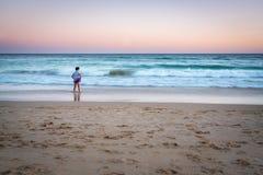 站立在与波浪的一个海滩的女孩长的曝光日落mage 库存图片