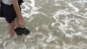 站立在与波浪击碎的一个海滩的女孩脚 股票视频