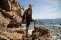 站立在与海洋的峭壁的登山人女孩在背景中 库存照片
