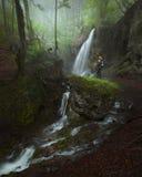 站立在与瀑布的大岩石的妇女在有薄雾的早晨 免版税图库摄影