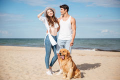站立在与狗的海岸的浪漫年轻夫妇 图库摄影