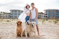 站立在与狗的海岸的浪漫年轻夫妇 库存照片