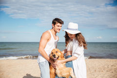 站立在与狗的海岸的浪漫年轻夫妇 免版税库存图片