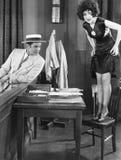 站立在与看她的腿的一个年轻人的一把椅子的少妇(所有的人被描述不是更长生存和前没有的庄园 免版税库存图片