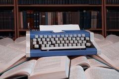 站立在与空白的纸片的开放书的打字机机智 库存照片