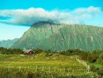 站立在与篱芭的一个领域的房子的被定调子的图象在与蓝天的一座大山附近 免版税图库摄影