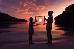 站立在与红色天空日落的海滩的母亲和女儿 免版税图库摄影