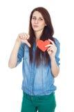 站立在与红色纸心脏的白色背景的牛仔布蓝色衬衣的美丽的女孩在手上 库存照片