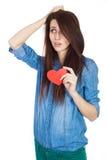站立在与红色纸心脏的白色背景的牛仔布蓝色衬衣的美丽的女孩在手上 免版税库存照片