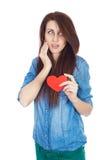 站立在与红色纸心脏的白色背景的牛仔布蓝色衬衣的美丽的女孩在手上 免版税库存图片