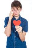 站立在与红色纸心脏的白色背景的牛仔布蓝色衬衣的英俊的年轻人在手上 图库摄影
