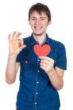 站立在与红色纸心脏的白色背景的牛仔布蓝色衬衣的英俊的年轻人在手上 免版税库存照片