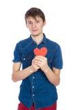 站立在与红色纸心脏的白色背景的牛仔布蓝色衬衣的英俊的年轻人在手上 库存图片