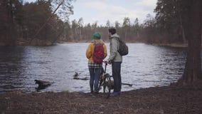 站立在与背包的河岸的游人年轻夫妇在他们的后面 人拿着自行车和妇女  股票录像