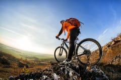 站立在与自行车的一座山顶部和享受谷视图的骑自行车者人在一个晴天反对蓝天 免版税库存照片