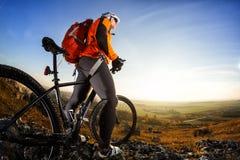 站立在与自行车的一座山顶部和享受谷视图的骑自行车者人在一个晴天反对蓝天 免版税库存图片