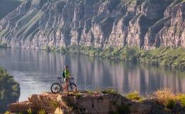 站立在与自行车的山的少妇在河上 免版税库存照片