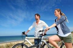 站立在与自行车的海滩的夫妇 库存图片