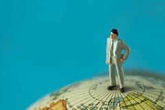 站立在与蓝色的地球地图顶部的微型商人 免版税库存图片