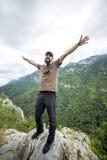 站立在与被举的胳膊的一座山顶部的远足者 库存图片