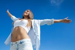 站立在与被举的胳膊的夏天领域的美丽的女孩 免版税库存图片