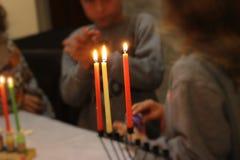 站立在与被点燃的蜡烛的Chanukah menora附近的孩子 图库摄影