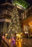 站立在与装饰的巨型圣诞树前面的妇女 图库摄影