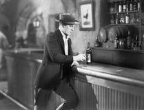 站立在与饮料的一个酒吧柜台的孤独的人(所有人被描述不更长生存,并且庄园不存在 供应商warr 免版税库存图片