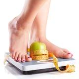 站立在与绿色ap的一个体重计的一个对女性脚 库存图片