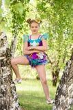 站立在两个桦树之间的逗人喜爱的年轻运动的白肤金发的女孩,戴colorfull体育泳装和金圆顶硬礼帽 免版税图库摄影