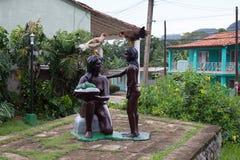 站立在两个雕象的两只公鸡 图库摄影
