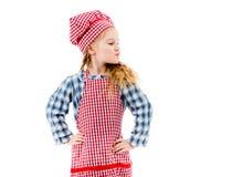 站立在两手插腰的姿势的红色格子花呢披肩围裙的女孩 库存图片