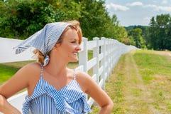 站立在乡下的近的篱芭和享受自然的俏丽的妇女 免版税库存照片